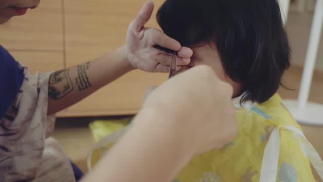 mutter schneidet sohn die haare zu hause - friseur lockdown stock-videos und b-roll-filmmaterial