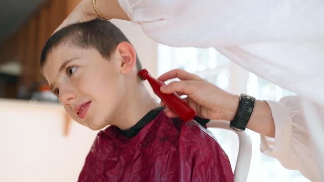 mutter schneidet die haare des sohnes mit haarschneider - friseur lockdown stock-videos und b-roll-filmmaterial