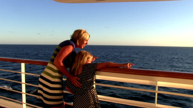 Mother daughter cruising during sunset pointing at sights on water video