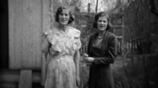 1933: Mother daughter in formal dress play wrestling in front yard.