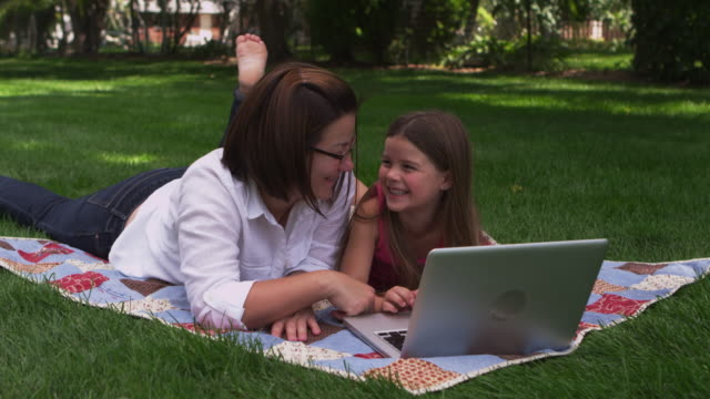 Mother daughter look at laptop video