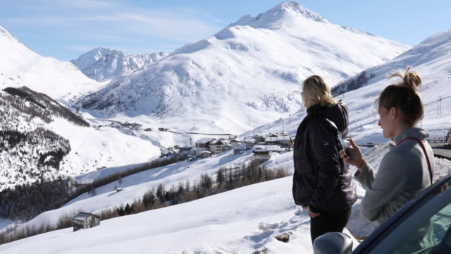 mother & daughter pause beside car, taking smart phone pics - livigno video stock e b–roll
