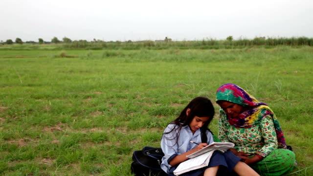 mor & dotter läsa utomhus i naturen - enbarnsfamilj bildbanksvideor och videomaterial från bakom kulisserna