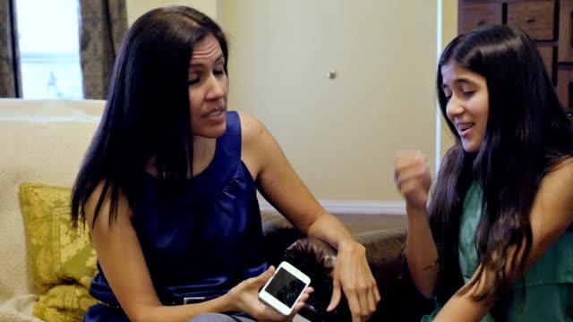 mor diskuterar trasiga smartphone med sin tonårsdotter - parent talking to child bildbanksvideor och videomaterial från bakom kulisserna