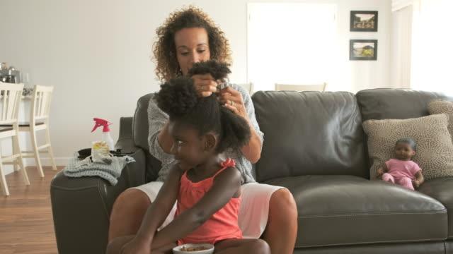 vídeos de stock e filmes b-roll de a mother doing daughter's hair - afro americano