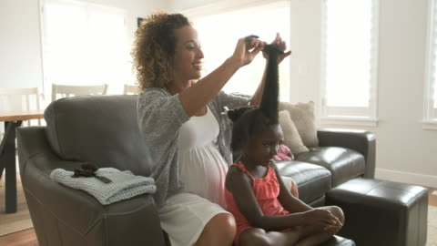 A Mother Doing Daughter's Hair A pregnant African American mother styles her daughter's hair in the living room of a home. black hair stock videos & royalty-free footage