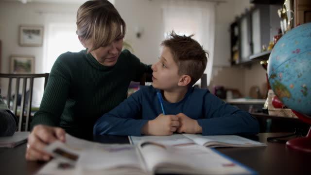 matka robi pracę domową ze swoimi synami - praca domowa filmów i materiałów b-roll