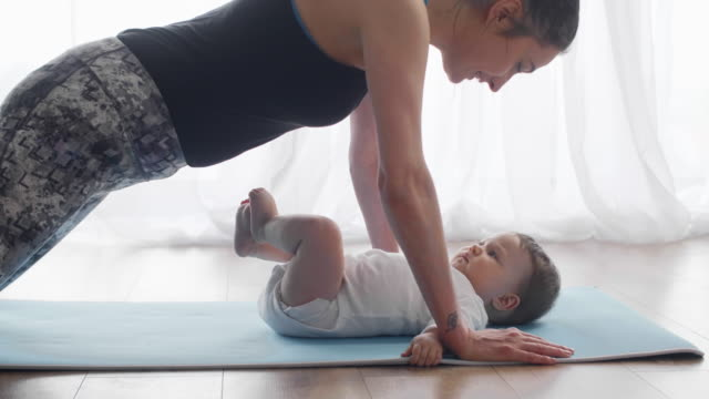 Mother doing push ups and kissing her baby Mother doing push ups and kissing her baby push ups stock videos & royalty-free footage