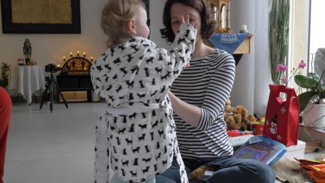 vídeos de stock e filmes b-roll de mother dressing toddler in bathrobe at christmas - pai solteiro