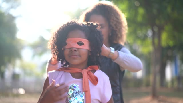 vídeos de stock e filmes b-roll de mother dressing up her daughter costume of super hero - afro latino mask