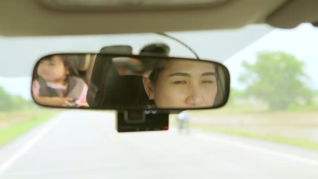 Mother driving a car, having her little baby girl in a child seat video