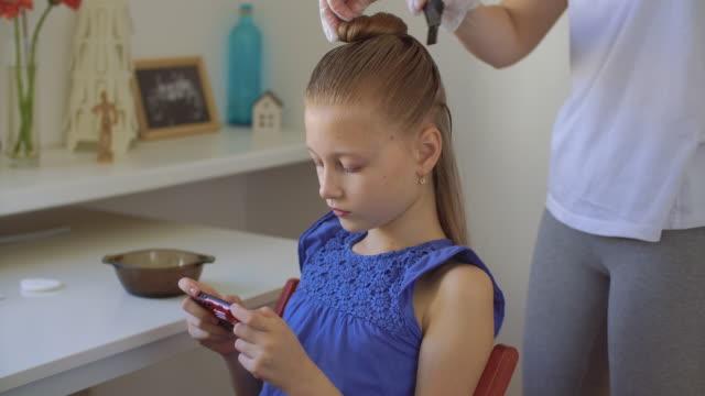 mutter färbt ihre tochter haare mit haarfärbemittel - haartönung stock-videos und b-roll-filmmaterial