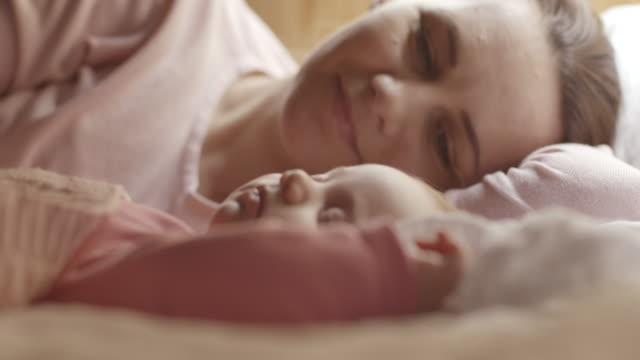 Mother enjoying while watching her sleepy baby