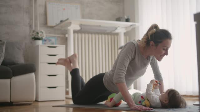 4 K : Mère avec son bébé exercice à la maison. - Vidéo