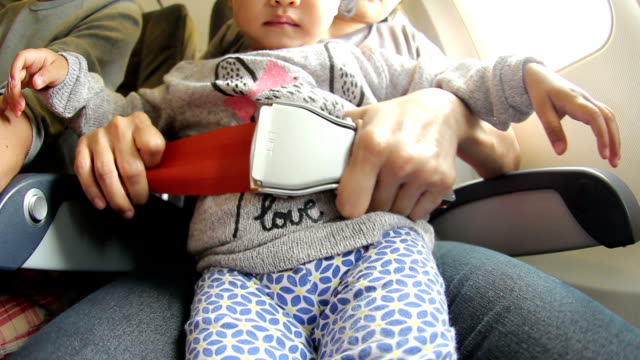HD : Mother Fastening Seatbelt for daughter on Airplane video