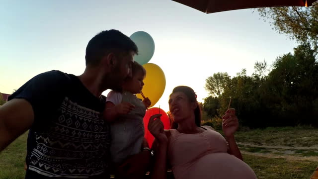 mother, father and baby daughter eating snacks in the park - mika video stock e b–roll