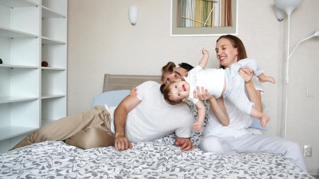 vídeos de stock e filmes b-roll de mother, father and their adorable kids playing together - super baby