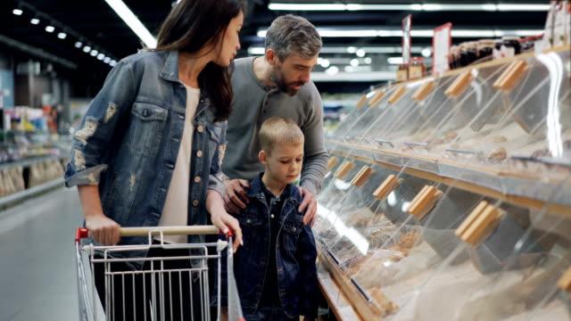 mutter, vater und sohn befinden sich einkaufsmöglichkeiten für lebensmittel in supermärkten zeigt auf kunststoffboxen in regalen und sprechen. großen lebensmittelgeschäft und seine mitarbeiter sind im hintergrund sichtbar. - wahlmöglichkeit stock-videos und b-roll-filmmaterial
