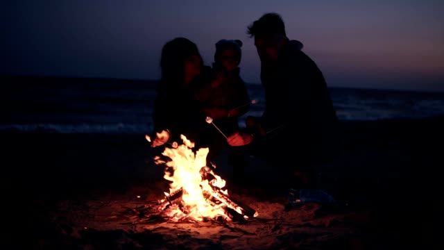 Mother, father in warm clothes are roasting marshmallows on wooden sticks with their little baby. Bonfire on the beach in the evening. Happy time together. Front view, close up video