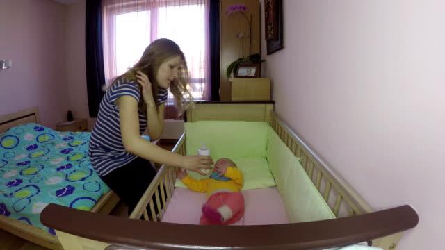 母は、ミルク パウダーのボトルと新生児の女の子をフィードしました。FullHD ビデオ