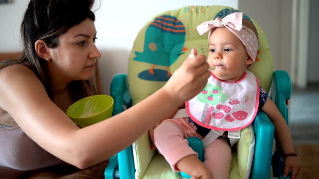 Mother feeding baby girl at home Mother feeding baby girl at home feeding stock videos & royalty-free footage