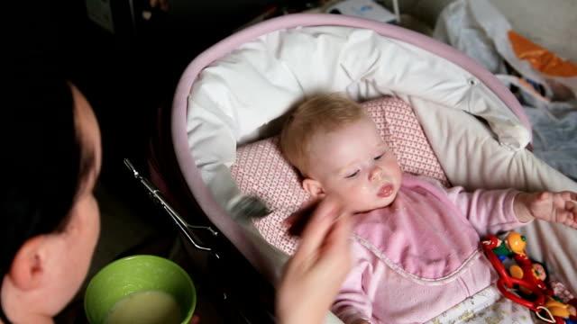 madre di nutrire il suo bambino con cucchiaio - 0 11 mesi video stock e b–roll
