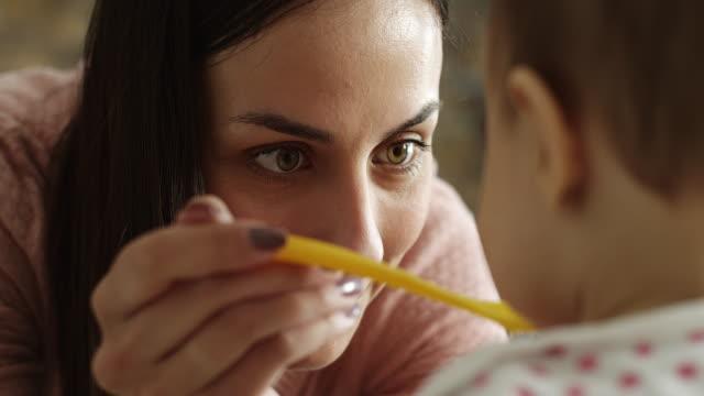 mother feeding her baby girl in kitchen - кормить стоковые видео и кадры b-roll