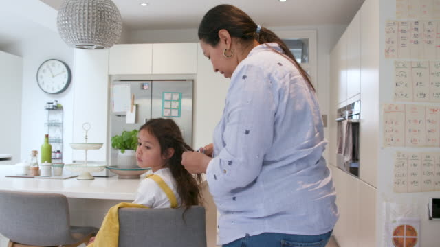 A mother fixes her daughters hair while she sits quietly