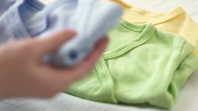 hd: madre passeggino pieghevole vestiti - abbigliamento da neonato video stock e b–roll