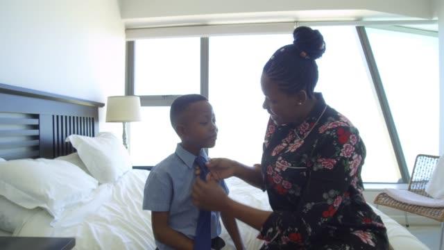 vídeos y material grabado en eventos de stock de madre prepara a hijo para la escuela lazo de fijación - corbata