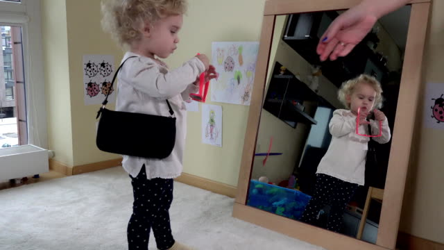 Mother give handbag and sunglasses for her daughter girl standing near mirror video