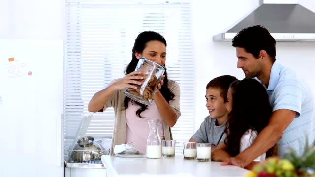 madre dando i cookie per la sua famiglia con latte - immergere video stock e b–roll