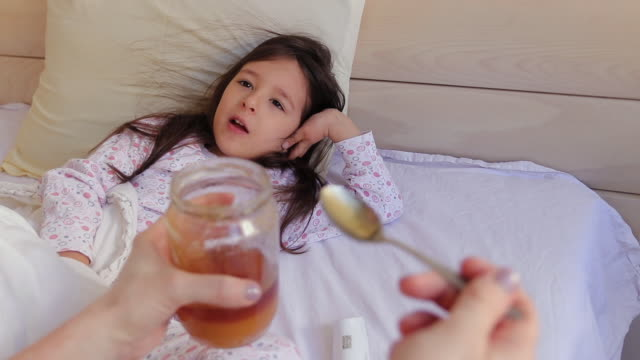 Mother giving honey to her daughter in bedroom at home Mother giving honey to her daughter to recover fast from illness, in bedroom at home double bed stock videos & royalty-free footage