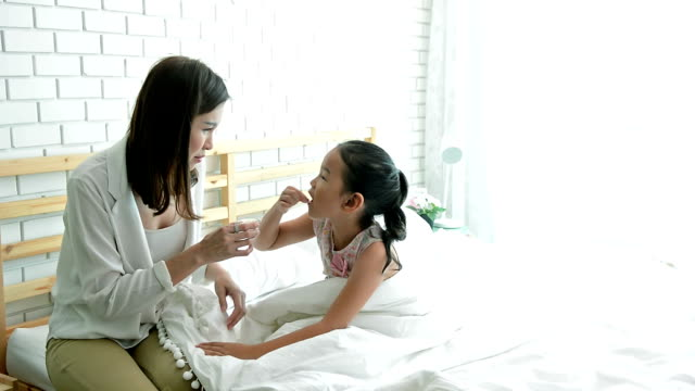 Mother giving medicine and drug to her daughter