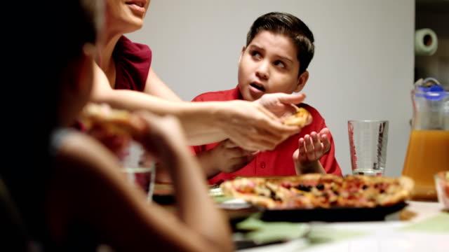 mother giving salad instead of pizza to overweight son - węglowodan jedzenie filmów i materiałów b-roll