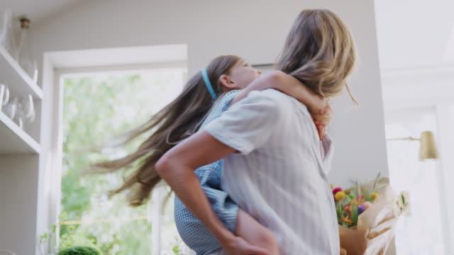mother giving smiling daughter piggyback ride in kitchen at home - один родитель стоковые видео и кадры b-roll
