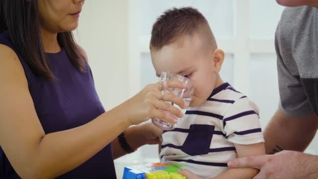 stockvideo's en b-roll-footage met moeder water geven met zijn zoontje in de keuken thuis, happy familie concept - glas serviesgoed