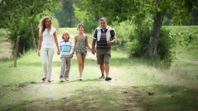 Mother, grandfather and children walking in the park video