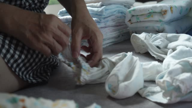 Mother hand Folding baby clothing concept at her home