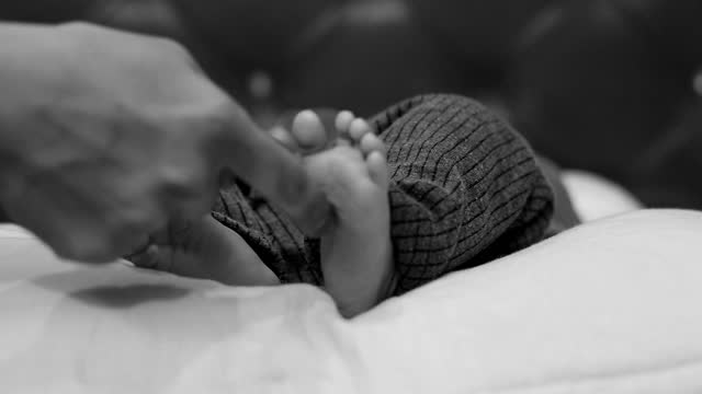 Mother hand touching baby feet video