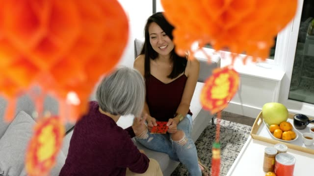 母親在農曆新年給女兒一個紅包 - chinese new year 個影片檔及 b 捲影像