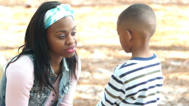 mor ha allvarliga prata med liten pojke på lekplats - parent talking to child bildbanksvideor och videomaterial från bakom kulisserna