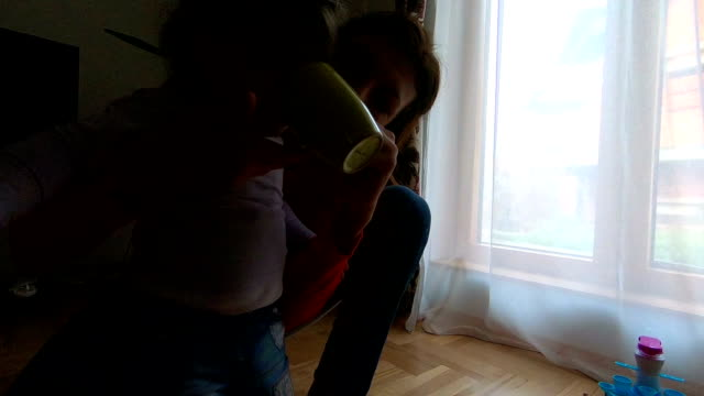 mother having tea party with daughter and toys in bedroom - mika video stock e b–roll