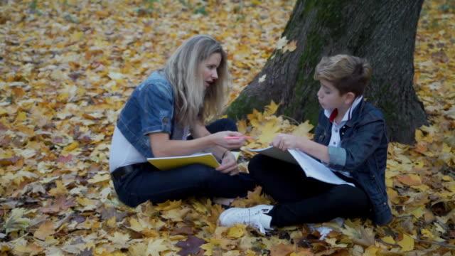 mor hjälp hennes son att göra läxor, familjen, sitta på hösten lämnar - linjerat papper bakgrund bildbanksvideor och videomaterial från bakom kulisserna