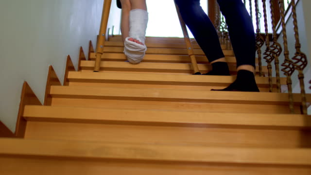 Mother help her son with broken leg to move down the stairs Mother help her son with broken leg to move down the stairs. The boy leans on the crutches and slowly moves down step by step. crutch stock videos & royalty-free footage