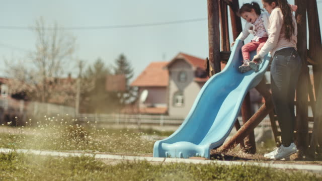mother help her toddler daughter to slide down in playground. stock video - scivolo video stock e b–roll