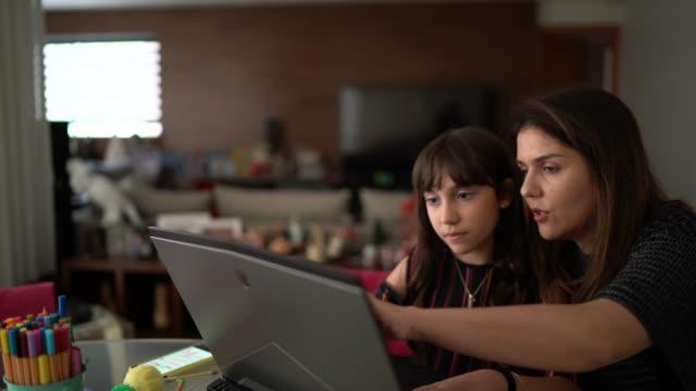 母は小さな女の子が家で勉強するのを助ける - ブラジル文化点の映像素材/bロール