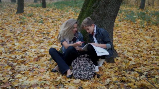 mamma hjälpa sonen att göra läxor - linjerat papper bakgrund bildbanksvideor och videomaterial från bakom kulisserna