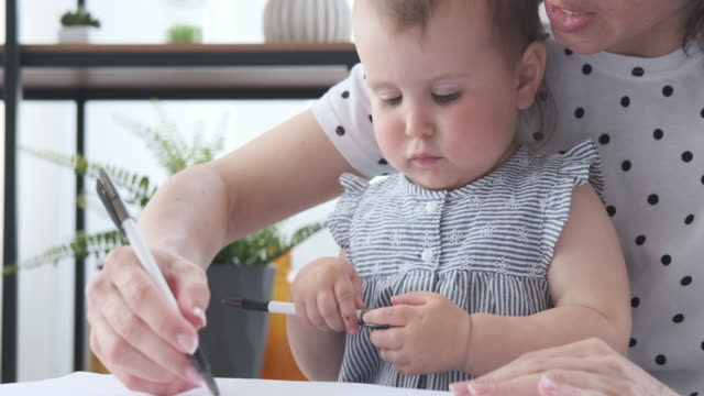 Mother helping baby daughter to draw on paper