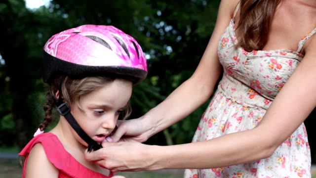 Mother Helping Child with cycling helmet. video